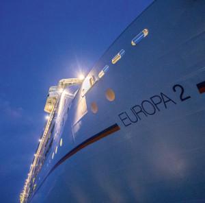 Abends auch mit Beleuchtung: Trutzig ragt der Rumpf der EUROPA 2 über dem Meer