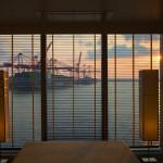 MS EUROPA 2: Auf dem Daybed im Spa-Bereich der Grand Ocean Suite genießt man einen letzten, vergoldeten Blick auf den Hafen. Der nächste Tag bringt neue Abenteuer.